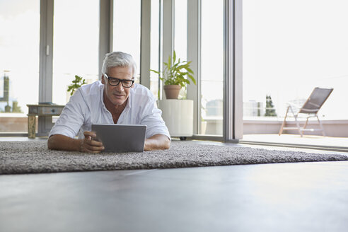Mature man lying on carpet at home using tablet - RBF06529