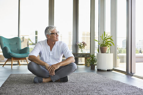 Mature man sitting on carpet at home looking out of window - RBF06532