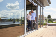 Smiling mature couple standing at roof terrace at home - RBF06535