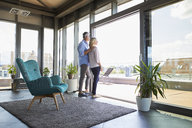 Mature couple looking out of window at home - RBF06538