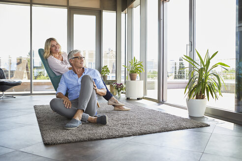Mature couple relaxing at home looking out of window - RBF06541