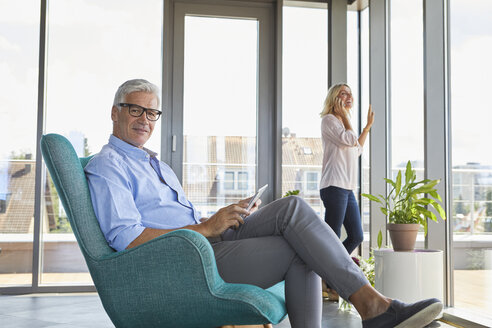 Mature couple relaxing at home using tablet and cell phone - RBF06547