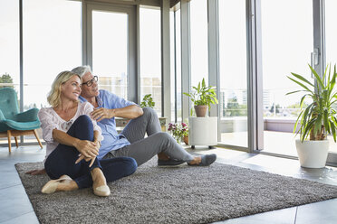 Smiling mature couple relaxing at home looking out of window - RBF06553