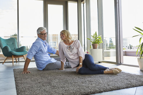 Smiling mature couple relaxing at home sitting on carpet - RBF06559
