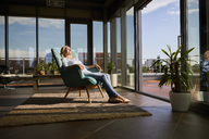 Mature woman relaxing in armchair in sunlight at home - RBF06565