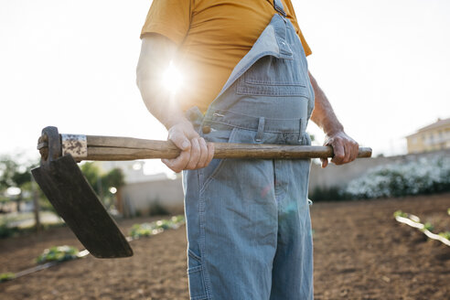 Senior man in denim holding shabby hoe tool and standing on cultivated land - JRFF01835