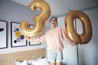 Portrait of cheerful woman with golden balloons, celebrating her birthday - ABIF00964