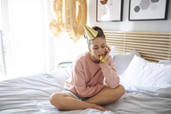 Bored and sad woman during her birthday, sitting alone on bed - ABIF00967