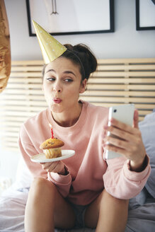 Woman blowing out the candle on the birthday cake and making a selfie - ABIF00976