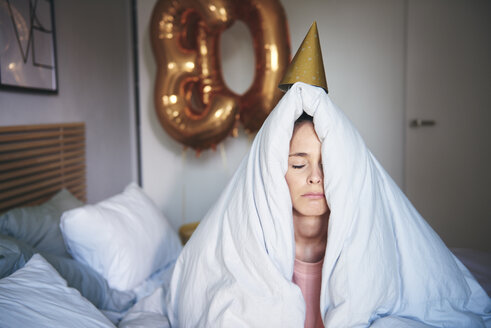 Sad woman celebrating her birthday, sitting on bed under blanket - ABIF00982