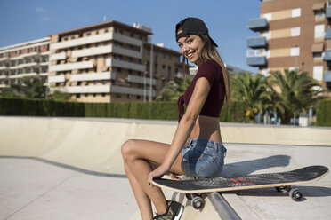 Young pretty woman sitting on wall of skatepark - JASF01943