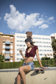 Young pretty woman sitting on wall of skatepark, listen music, using digital tablet - JASF01946