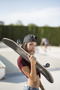 Young woman in skate park, carrying skateboard - JASF01949