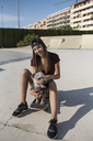Young woman sitting on skateboard, stroking her dog - JASF01955