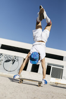 Back view of man in stylish sportive outfit standing on skateboard upside down against blue sky - JRFF01845