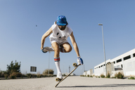 Man in stylish sportive outfit standing on skateboard against blue sky - JRFF01851