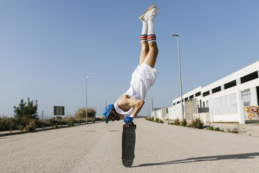 Man in stylish sportive outfit standing on skateboard upside down - JRFF01854