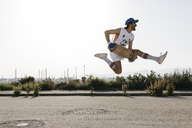 Sportive man jumping above ground with skateboard on hands - JRFF01860
