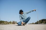 Trendy man in denim and cap skateboarding - JRFF01863