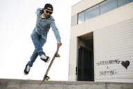 Trendy man in denim and cap skateboarding, doing jump with skateboard from concrete ramp - JRFF01866