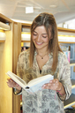 Portrait of smiling young woman with  book at the library - IGGF00565