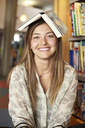 Portrait of smiling young woman with book on top of head at the library - IGGF00571