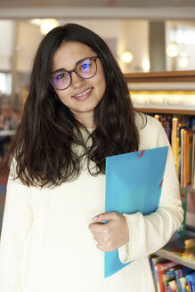 Portrait of smiling young woman with folder at the library - IGGF00574