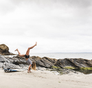 Young woman with surfboard doing handstand on the beach - UUF15029