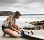 Young woman at the beach preparing surfboard - UUF15032