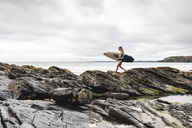 Young woman carrying surfboard on a rocky beach at the sea - UUF15035