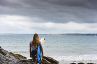 Young woman carrying surfboard on a rocky beach at the sea - UUF15038