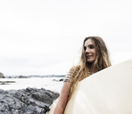 Young woman on the beach carrying surfboard, portrait - UUF15044
