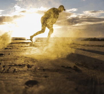 Man doing movement training at the beach with colorful smoke at sunset - UUF15056