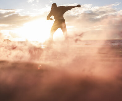 Man doing movement training at the beach with colorful smoke at sunset - UUF15059