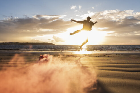 Man doing movement training at the beach with colorful smoke at sunset - UUF15062