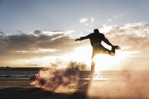 Man doing movement training at the beach with colorful smoke at sunset - UUF15065