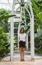 Beautiful woman standing in greenhouse - KKAF01651