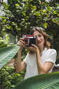 Young woman in greenhouse, taking pictures with an instant camera - KKAF01669