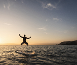 Young man jumping from paddleboard into water at sunset - UUF15091