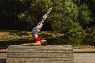 Young woman practicing Pilates in an urban park - NMSF00230