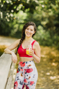 Young woman drinking juice after practicing Pilates in an urban park - NMSF00236