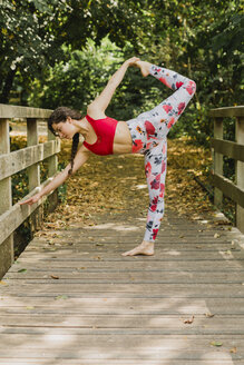 Young woman practicing Pilates in an urban park - NMSF00242