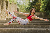 Young woman practicing Pilates in an urban park - NMSF00245