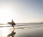 Young man running on beach, carrying surfboard - UUF15114