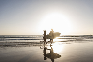 Young couple running on beach, carrying surfboard - UUF15120