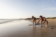 Young man showing young woman how to surf on the beach - UUF15129