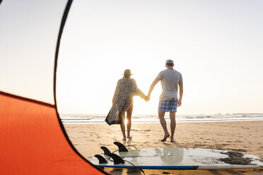 Romantic couple camping on the beach, doing a beach stroll at sunset - UUF15147