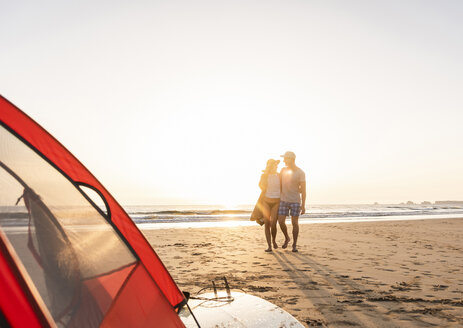 Romantic couple camping on the beach, doing a beach stroll at sunset - UUF15150