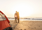 Romantic couple camping on the beach, embracing at sunset - UUF15153