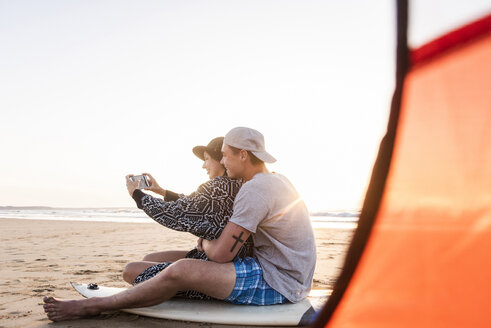 Couple camping on the beach, taking smartphone selfies - UUF15156